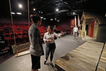 Working on scenery positioning with cast member Garret Storms, left, Emily Scott Banks is directing her third play for Stage West in Fort Worth.
